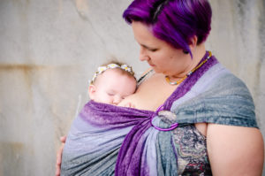 Image of a sleeping baby worn in a grey and purple ring sling with purple rings by a white babywearer with vibrant purple hair.