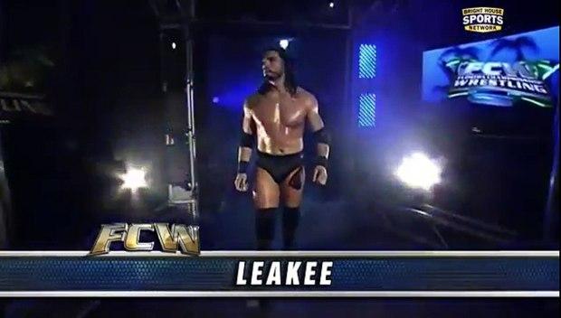 """Roman Reigns entra no ringue, com seu antigo nome """"Leakee"""" sendo mostrado na altura da sua canela."""