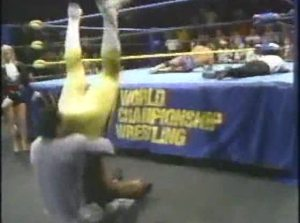 Rick Rude delivering a piledriver to Simmons on the floor.