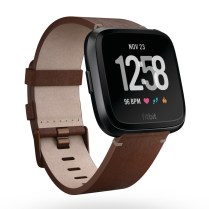 Product render of Fitbit Versa in 3 quarter view in cognac Horween leather and black aluminum case showing default clock