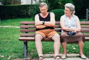 Image, mature couple sitting on park bench, the man is dozing.