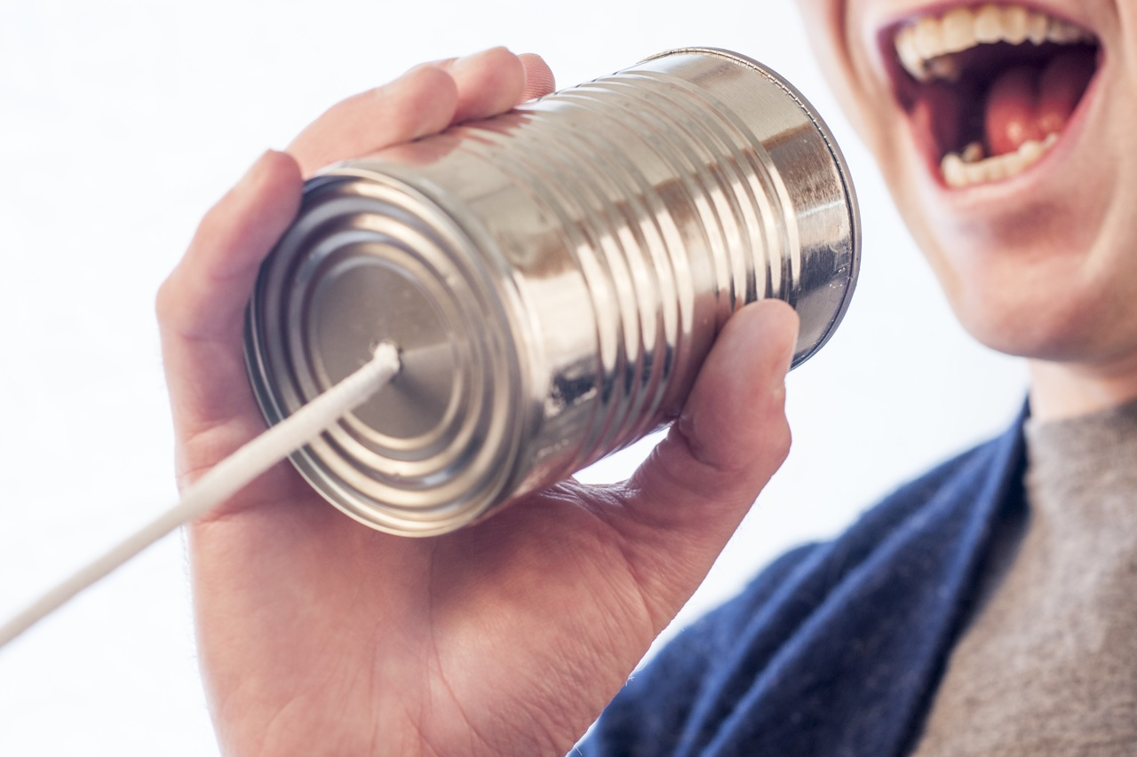Image, man shouting into tin can telephone.