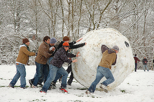 Image, Crowd of men rolling a giant snowball.