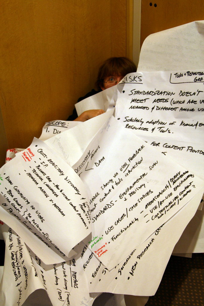 Image, person buried under piles of notes.