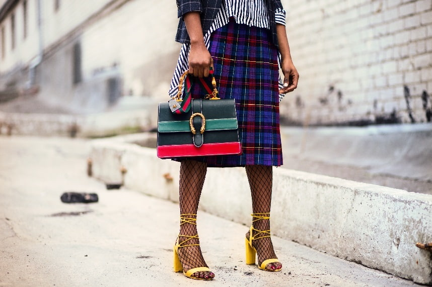 Image, Woman with yellow high heels, fishnet stockings, tartan skirt, stripy shirt, checked jacket, and stripy bag.