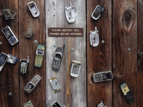 Image, old cell phones nailed to a door, with a sign saying 'Please destroy cell phones before entering'.