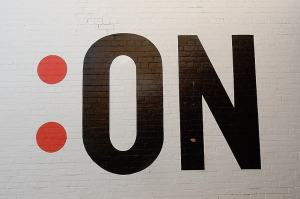 Image of a colon and the word 'on' painted on a brick wall.