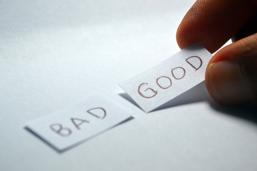 Image, Hand laying down slips of paper with the words 'Bad' and 'Good' written on them.