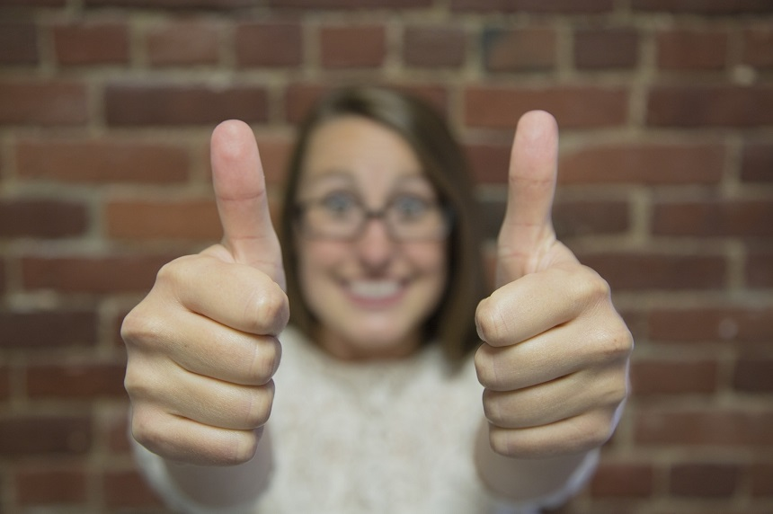Image, woman wearing glasses giving the thumbs up sign