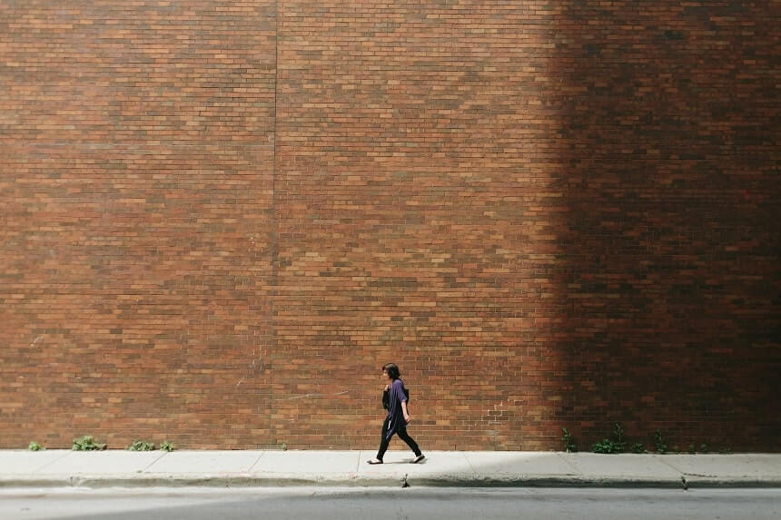 Image, dark haired human walking past a very high brick wall