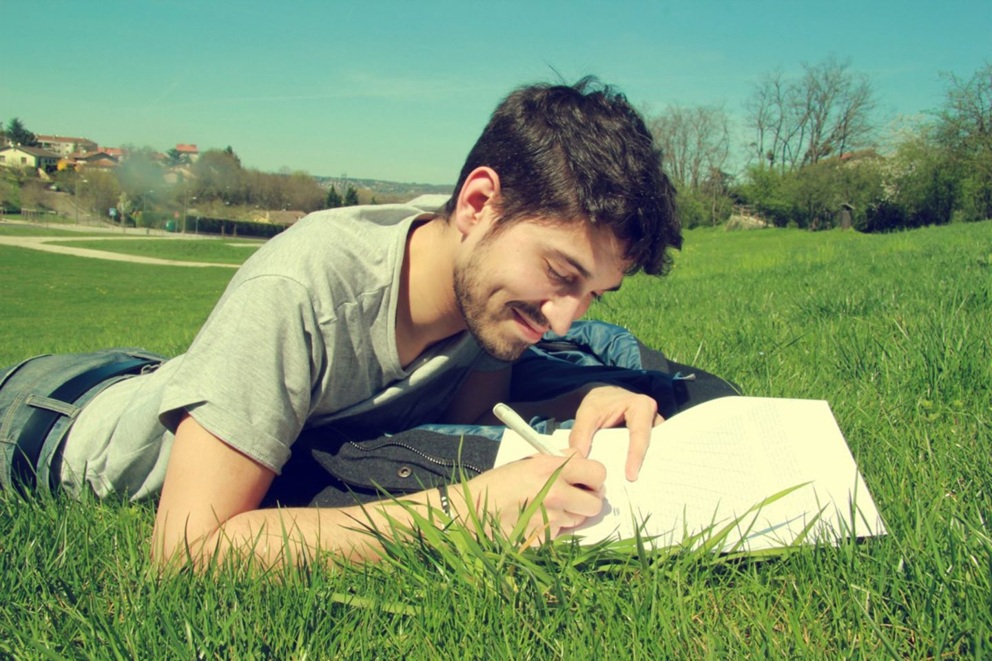 Smiling man writing on paper in a grassy field