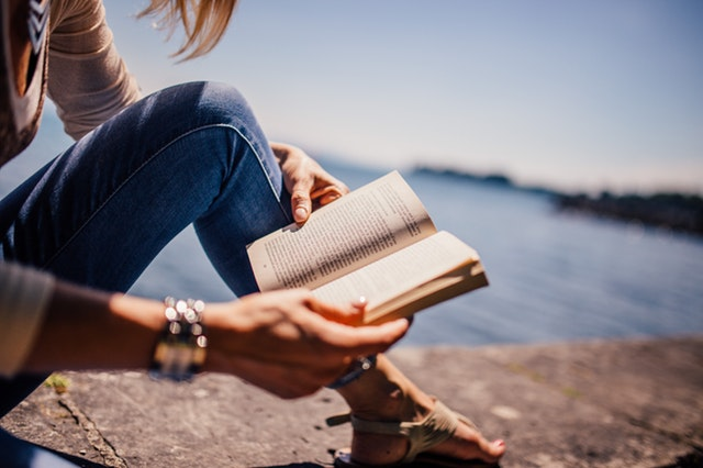 Woman reading an open book on a stone wall by water