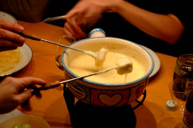 Fondue on a table, bread on two forks dipping in