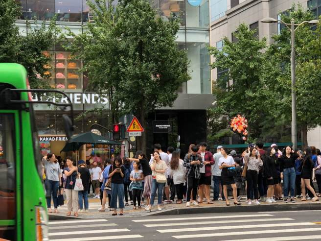 People waiting to cross the road in Seoul as a green bus departs