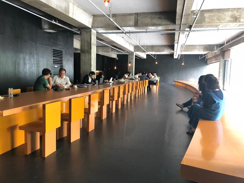 Long table and long curved bench with coffee drinkers in a converted warehouse