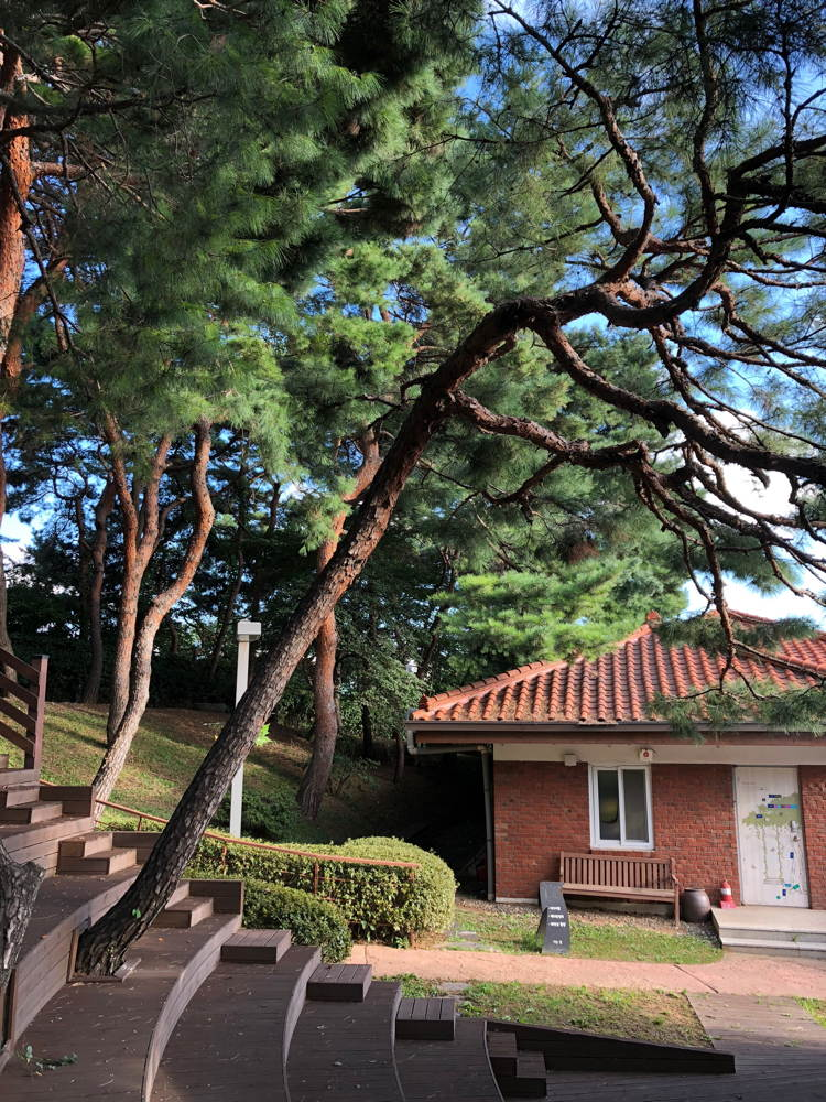 Pine trees, steps, and a brick building of Yeonhui writers' residence.