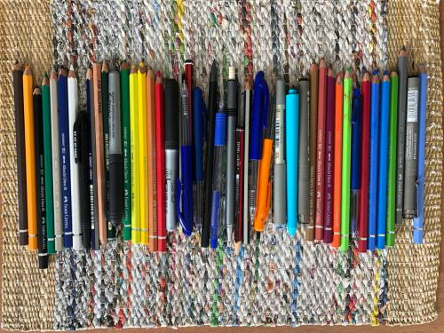 Photo of many pencils and pens on a table mat