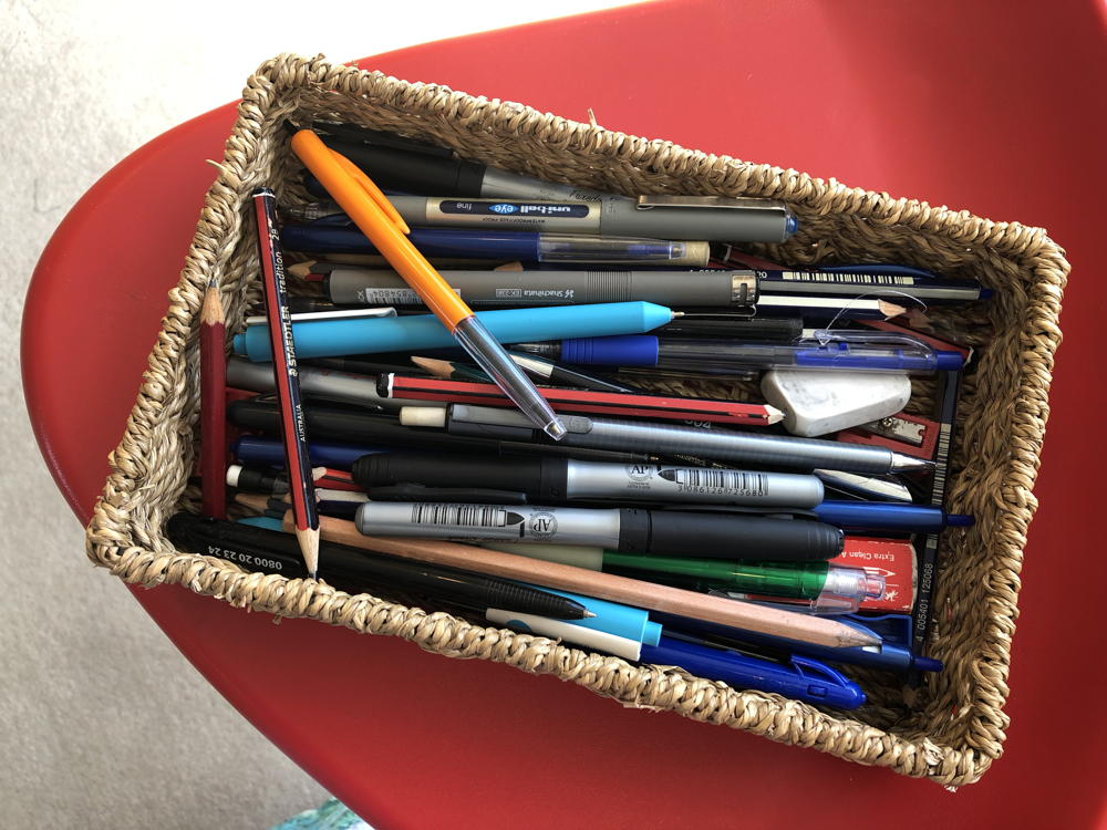 Random pens, pencils and erasers in a fibre box