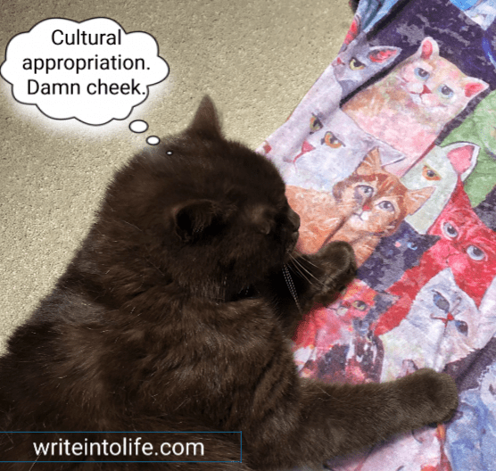 "Black cat looking at cats on a tee shirt. Thought bubble says, ""Cultural appropriation. Damn cheek."" Writeintolife.com"