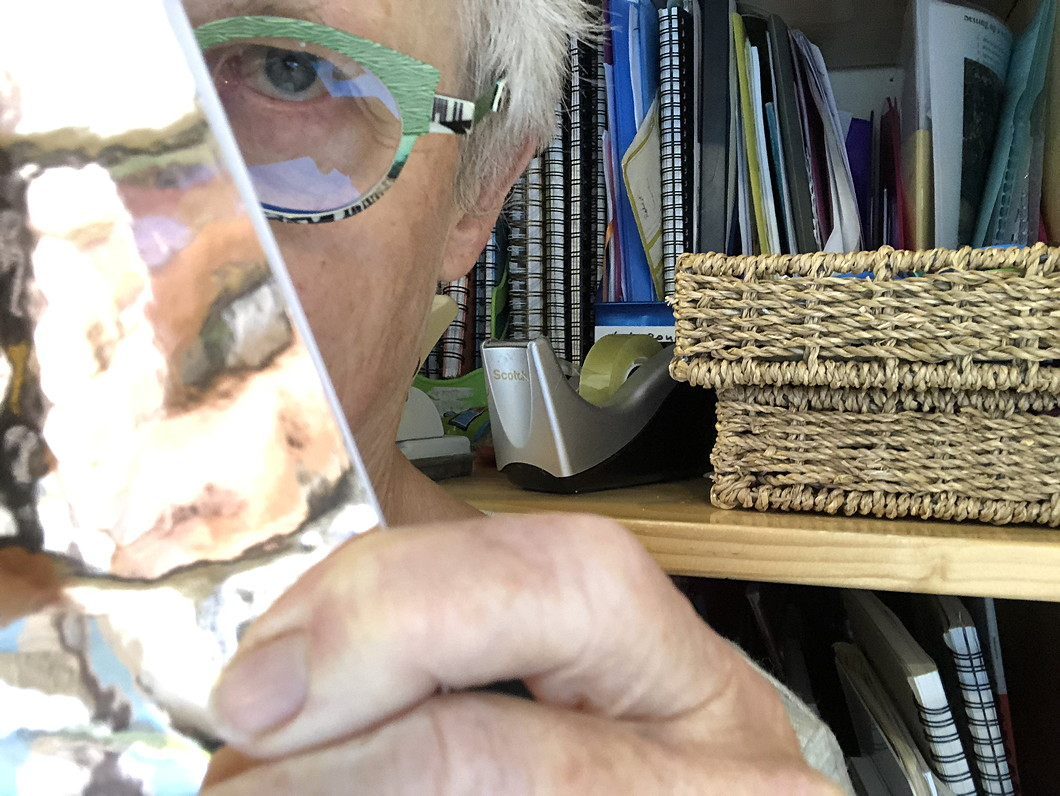 Photo of author hiding behind a notebook. Files and notebooks in the background