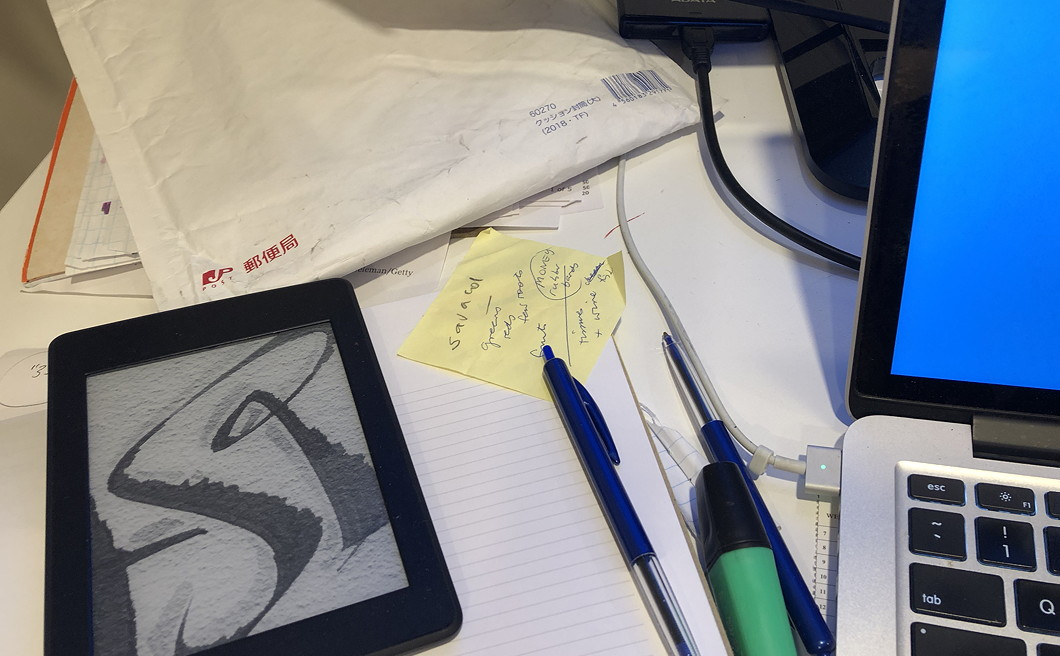 Photo of a messy desk with notebooks, pens, Kindle, envelope and computer