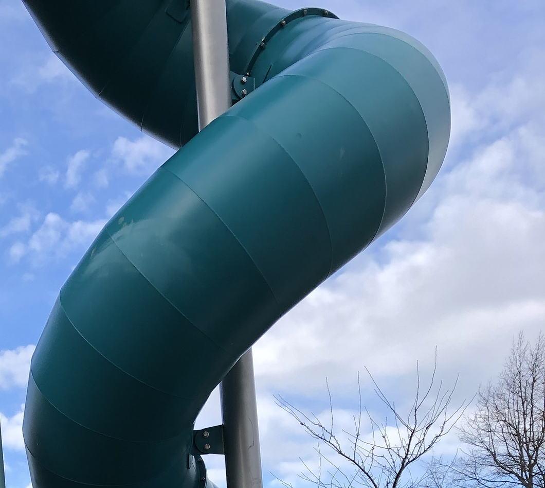 Photo of a children's tube slide against blue sky