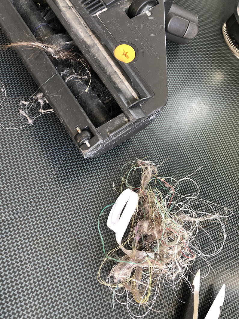 Dirty vacuum cleaner roller-brush with a muddle of threads