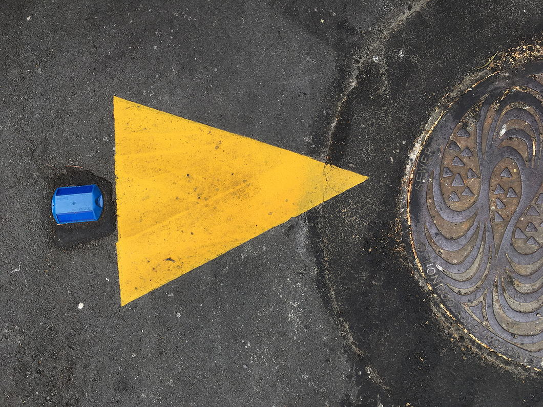 On the footpath, a blue bolt, yellow triangle and metal manhole cover