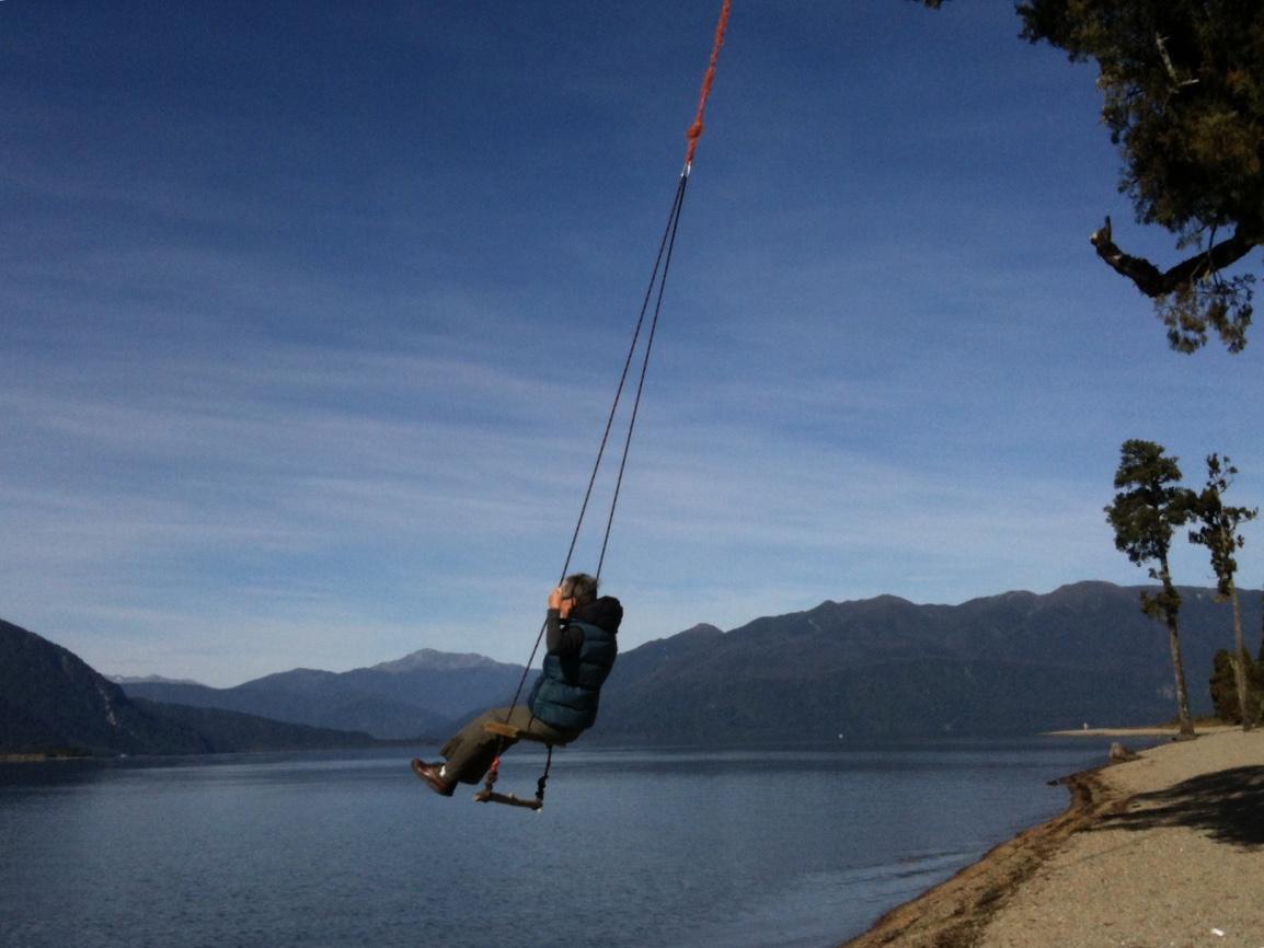 woman swinging over a lake near Moana, West Coast, New Zealand