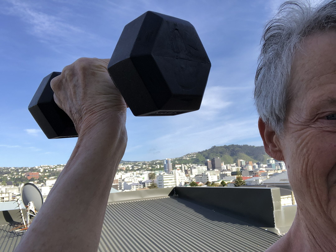 old person lifting a weight on a rooftop