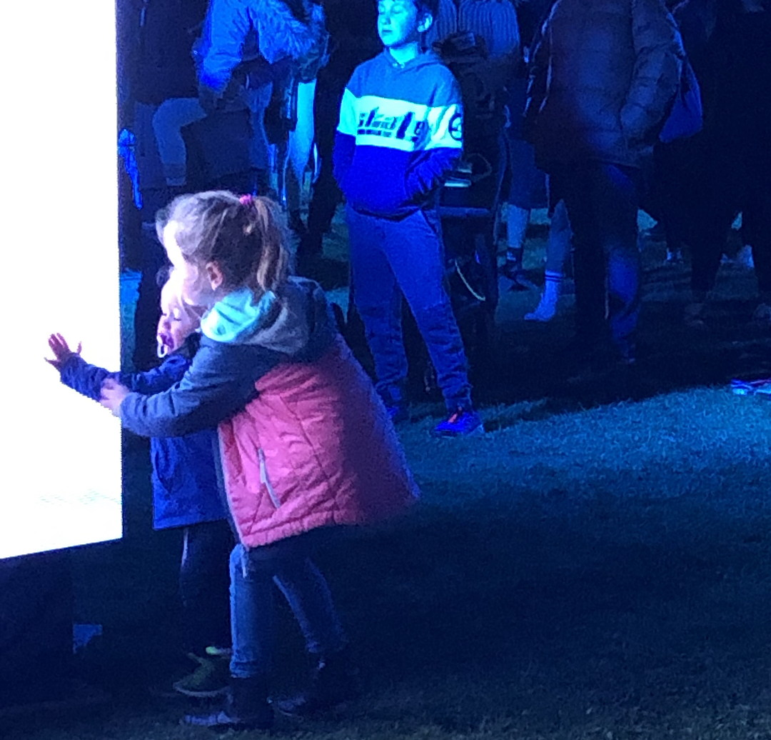 two children touch a big screen with fascination and delight