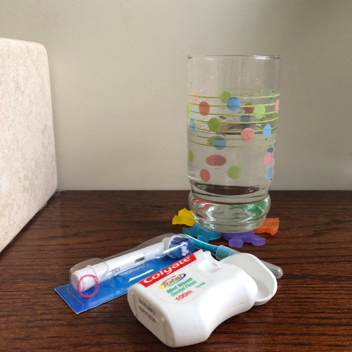 photo of a glass of water, dental floss and toothbrush