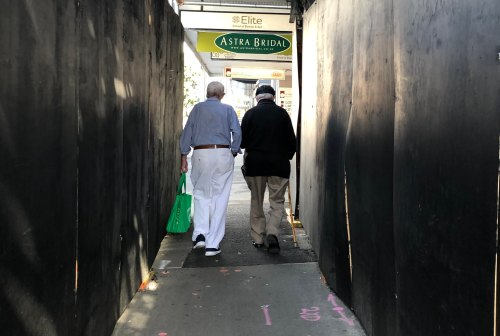 Preventing loneliness: two older men walking together with shopping bags