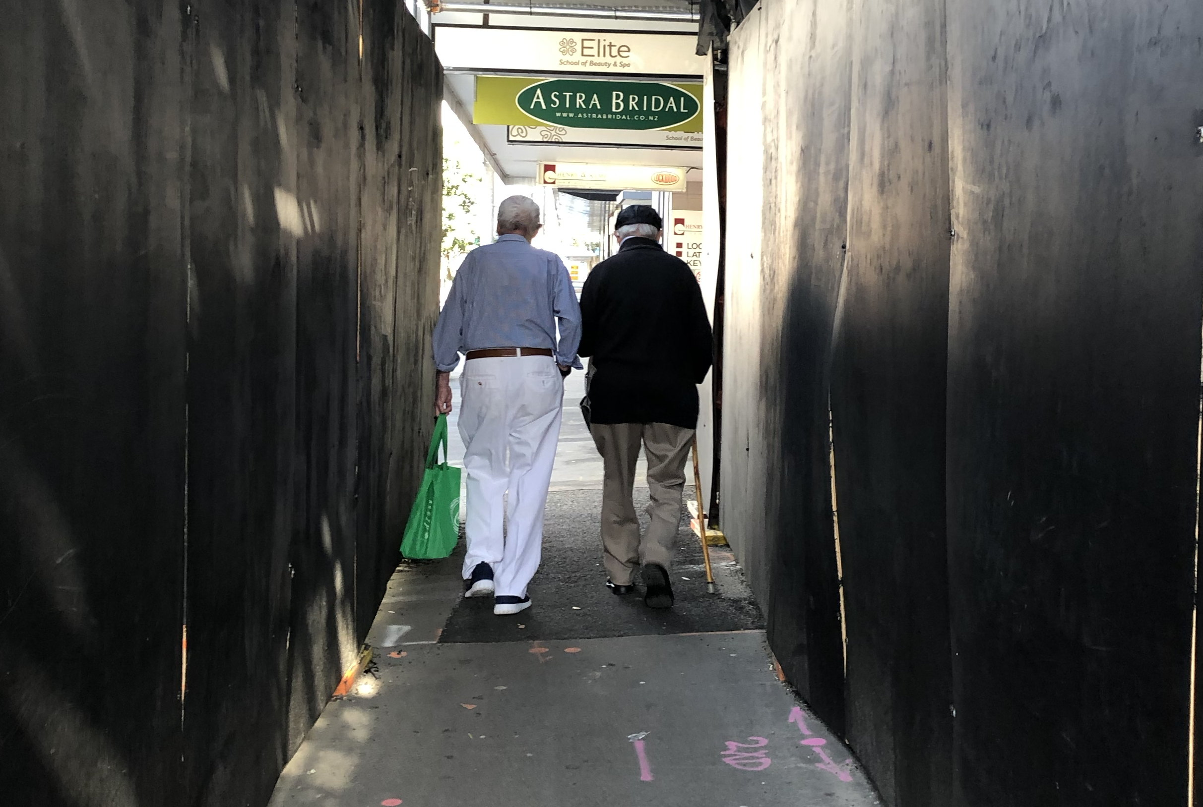 two older men walking together with shopping bags