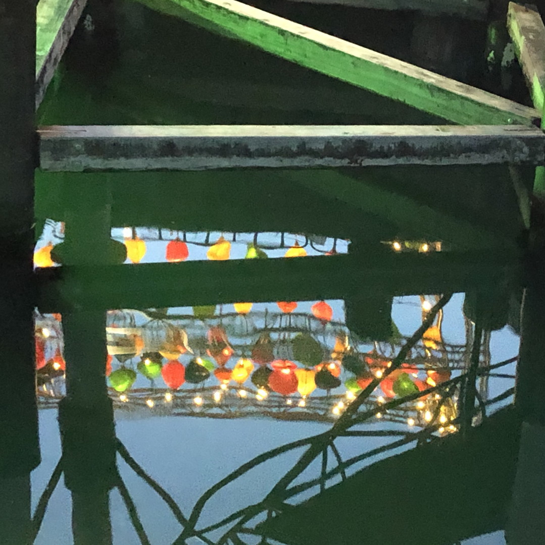 reflections of colourful lanterns in water below wharf structures