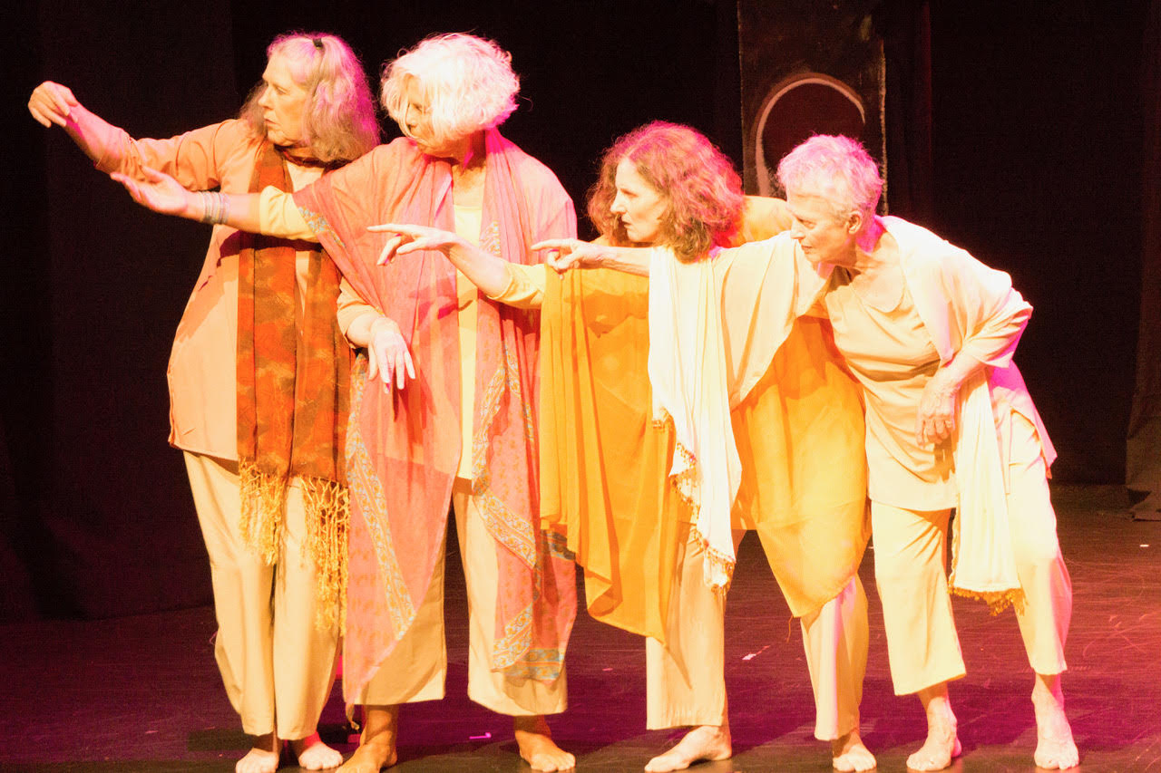 4 older women dancers in costume, pointing ominously