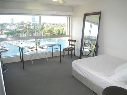 Photo inside very small apartment with view of yachts in Rushcutters Bay