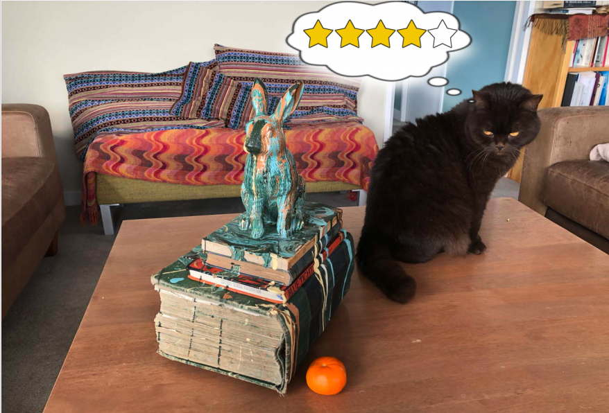 Cat contemplates art object, rabbit perched on books spattered with paint, and gives it four stars