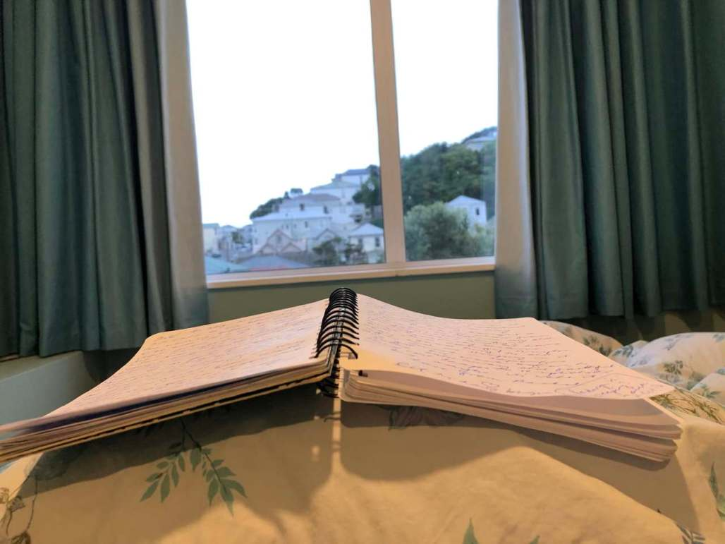 notebook with pages of longhand writing open on a bed