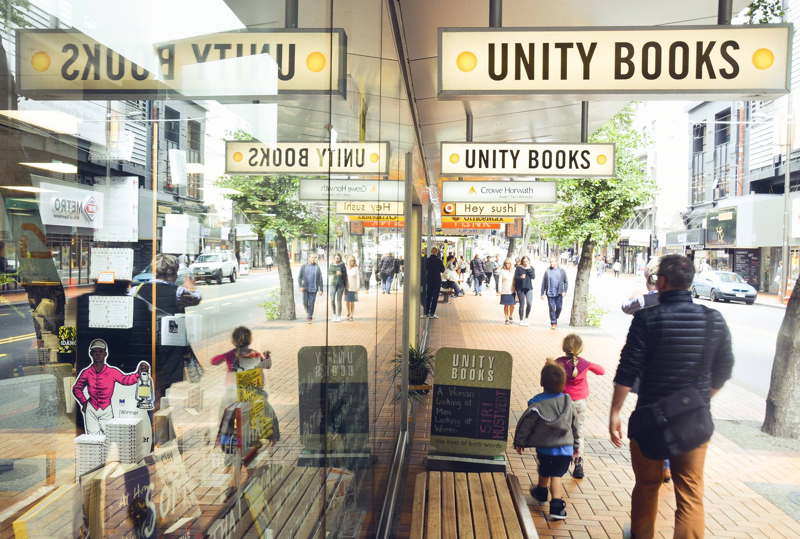 Photo of Unity Books shopfront with passersby reflected in the windows