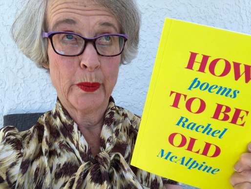 Woman pulls an ugly face while holding a bright yellow and pink book called How To Be Old,Poems by Rachel McAlpine
