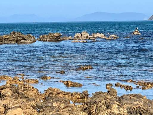 View of blue sea, rocks in foreground, hills in the distance