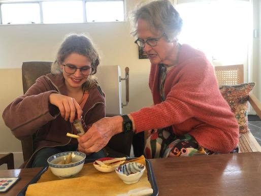 A young poet and an old poet examine chili flakes, green apple and cheese slices