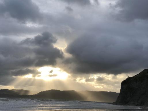 Photo of dark clouds over dark sea and shoreline, lit by a dramatic sunburst