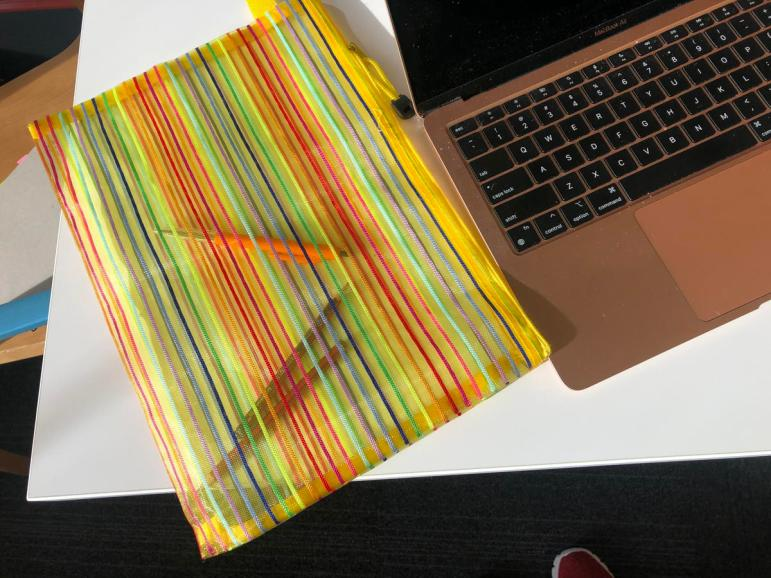 photo of MacBook Air and a sip bag Pontaining pens and pencils