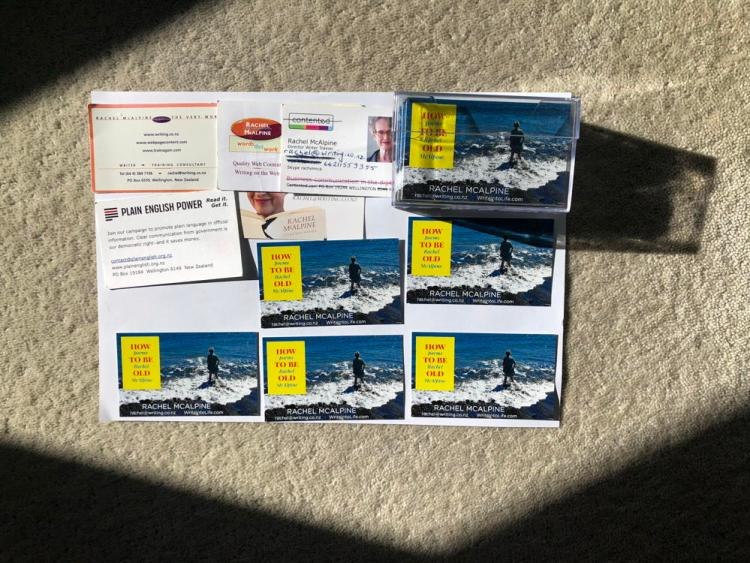 6 business cards for the same person arranged on a sheet of paper. One dominates, showing cover of How To Be Old and a photo of a woman paddling in the sea.