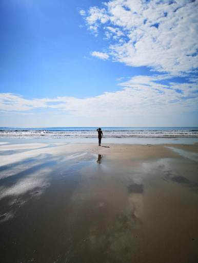 One person standing on a vast beach under a blue sky