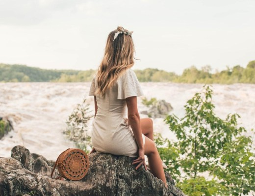 Girl sitting on a rock looking out at a flowing river