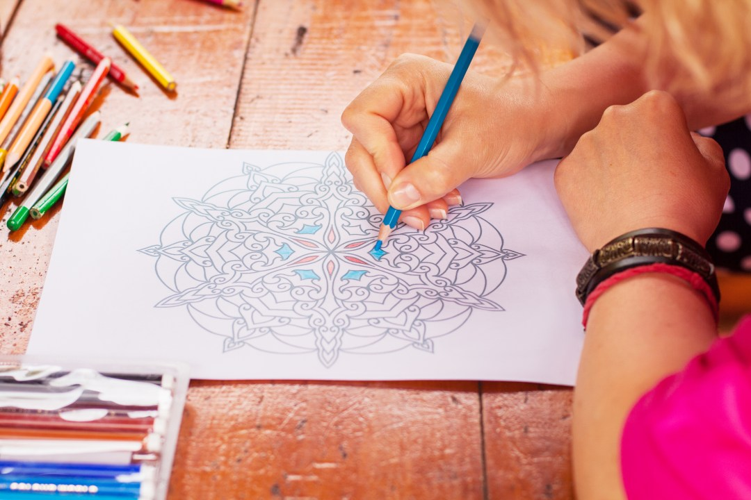 Closeup of woman's hand drawing mandala with a blue pencil on the wooden table
