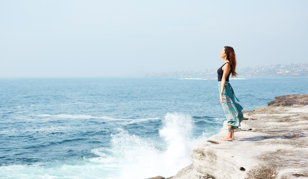 Girl standing at the beach with waves crashing on the rocks